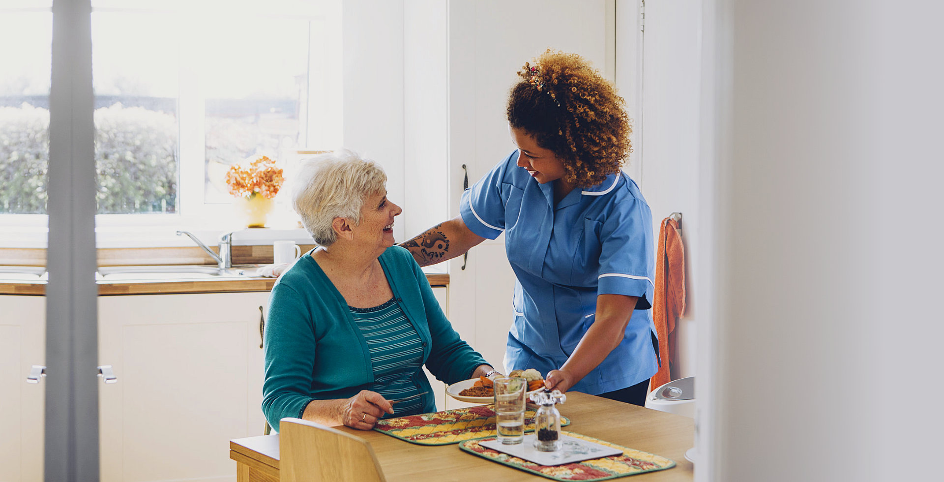 caregiver and elderly woman smiling each other