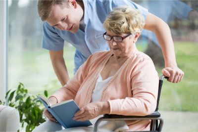 Elderly woman and caregiver reading a book